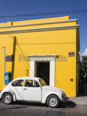 yellow building and white vw bug