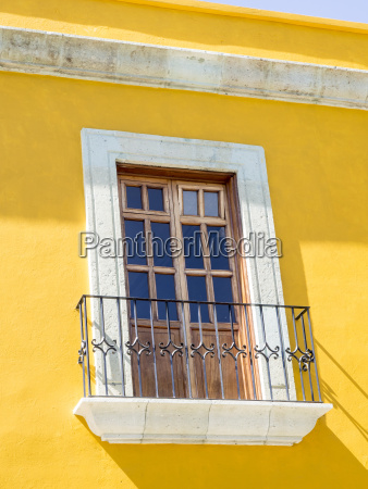white window of yellow house oaxaca
