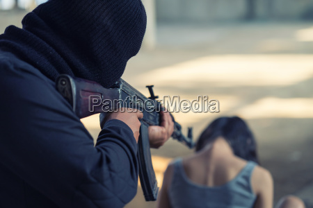 man in balaclava threatening with gun