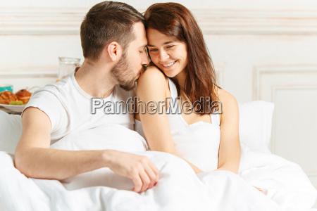 young adult heterosexual couple lying on