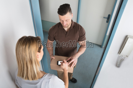 young woman signing after receiving delivery