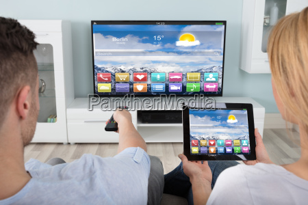 couple watching television using digital tablet