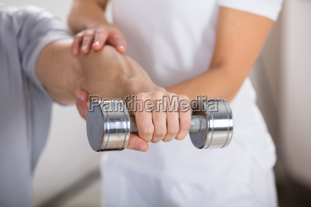 physiotherapist helping man to exercise