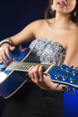 teenage girl playing guitar close up