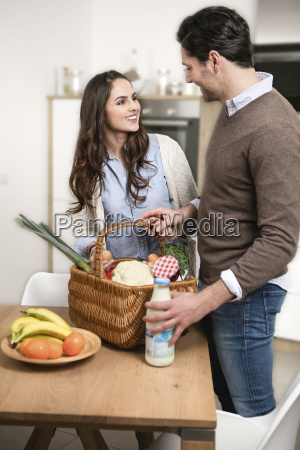 young couple unpacking purchase on kitchen