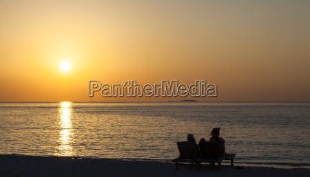 asia tourist looking sunset at beach