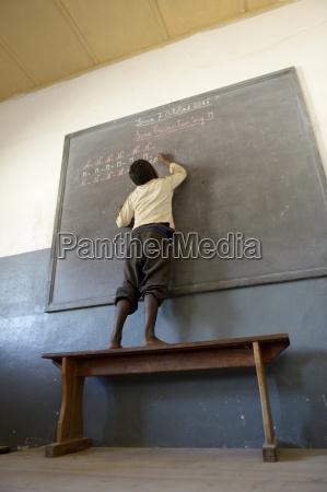 madagascar fianarantsoa schoolboy writing on blackboard