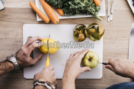 hands of couple cutting fruits for
