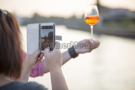 woman photographing beverage with her smartphone