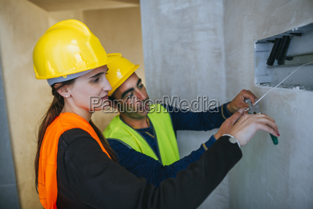male and female electrician working on