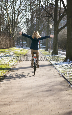 blond woman riding bike with arms