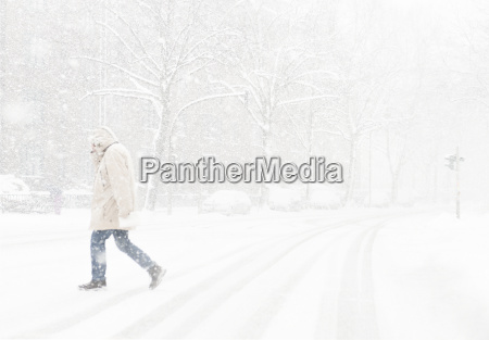 pedestrian crossing street in blowing snow