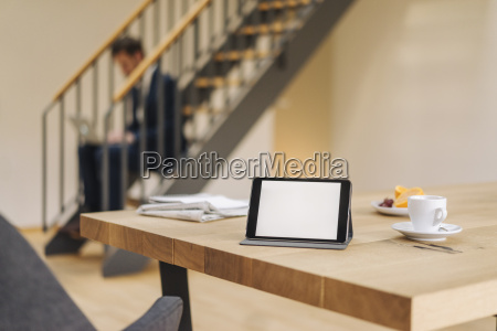 tablet on table with businessman on
