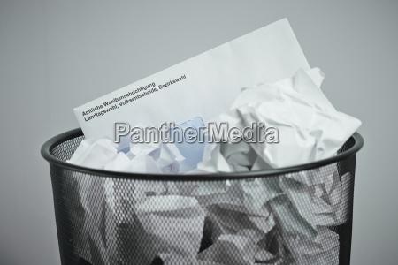 election voting card in wastepaper basket