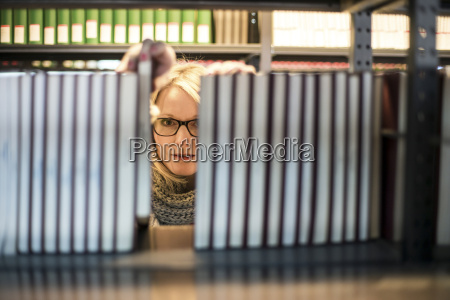woman in library looking from behind