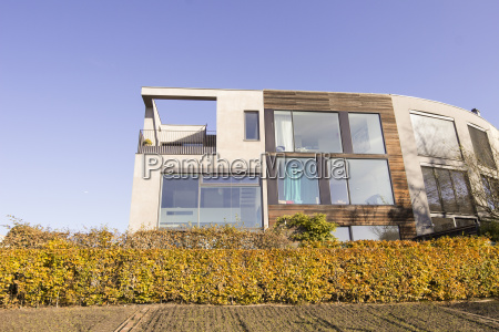 modern residential house behind autumnal hedge
