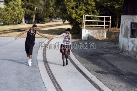 stylish young couple holding hands