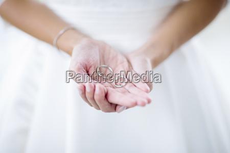 brides maid holding wedding rings