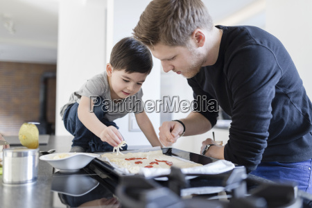 father and son preparing pizza in