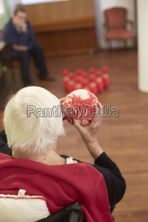 age demented senior woman bowling with