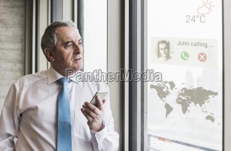 businessman receiving a call on windowpane