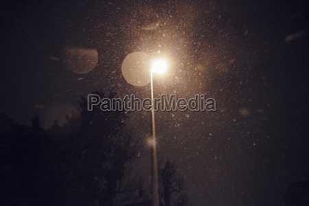 snowfalll at night under street lantern