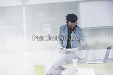 young businessman sitting on desk working