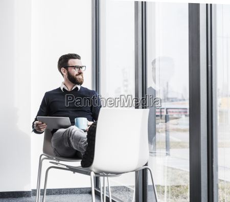 young businessman sitting on chair using