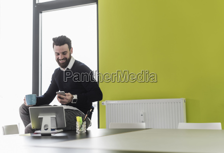young businessman sitting in office using