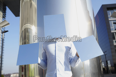 man hidden behind light blue rectangles
