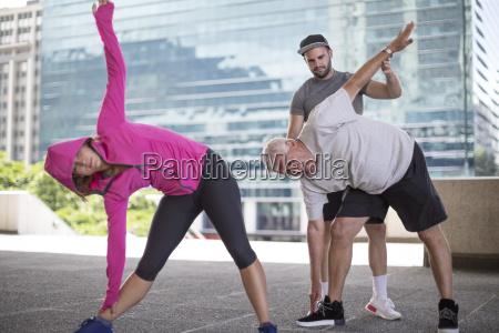 fitness instructor guiding senior man doing