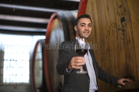 young man testing red wine at
