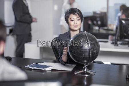 woman looking at globe sitting at
