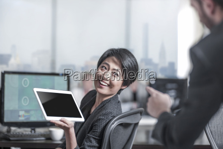 smiling woman showing tablet to colleauge