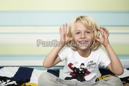 mischievous blond boy on bed