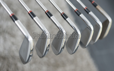 row of golf clubs close up
