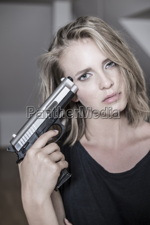 portrait of depressed woman holding pistol