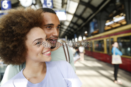 happy young couple waiting for commuter