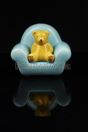 figurine of teddy bear on chair