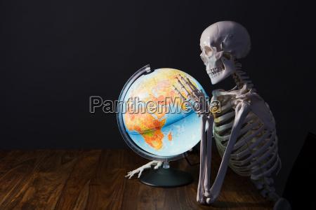 skeleton holding globe