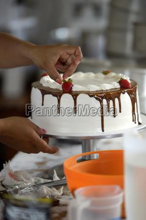 pastry cook decorating cream cake close