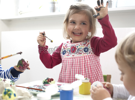 children painting easter eggs