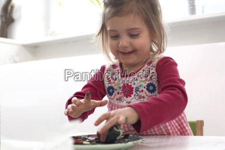 smiling little girl painting easter egg