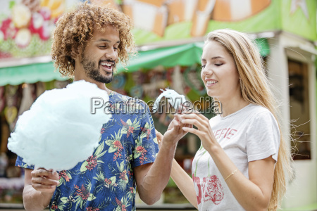 young couple eating candy floss at