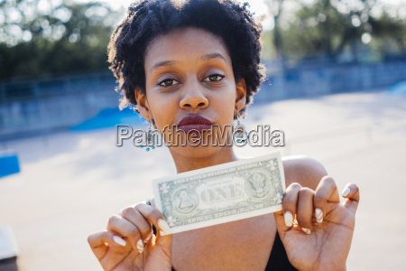 portrait of woman showing one dollar