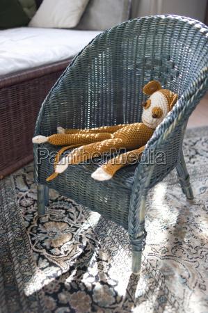 crocheted toy monkey on wicker chair