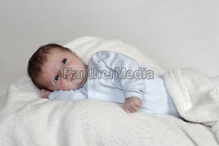 three weeks old baby boy lying