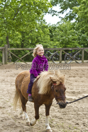little girl riding on pony
