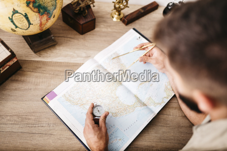 young man planning journey using compasses
