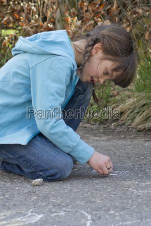 germany tuebingen girl drawing hopscotch on